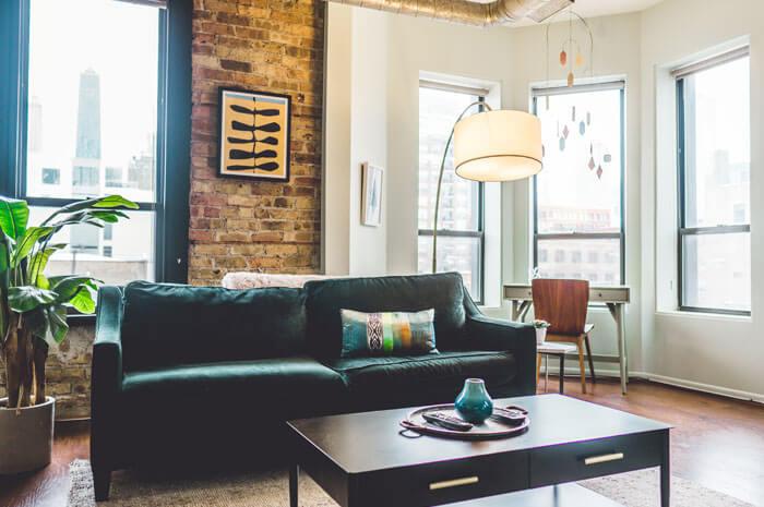 Apartment interior with dark green sofa and floor lamp.